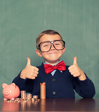 Boy wearing sweater and bowtie with two thumbs up and piggy bank and coins on table